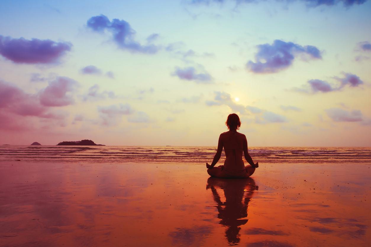 Woman meditating in sunset beach