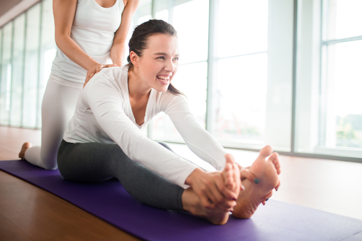 Active girl sitting on mat while her instructor helping her to make stretching